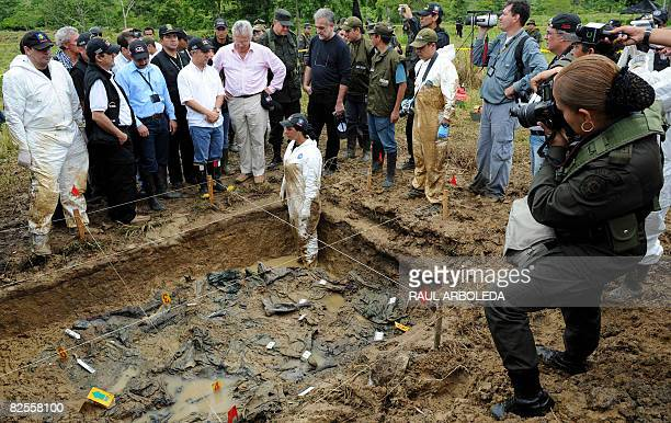 A Colombian police officer takes pictures of a paramilitary mass grave with the presence of Prosecutor of the International Criminal Court Luis...