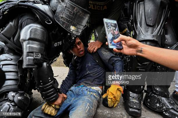 Colombian police officers arrest a demonstrator during a protest against the government in Cali, Colombia, on May 10, 2021. - Faced with angry street...