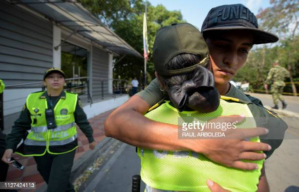 A Colombian police officers embraces a member of the Bolivarian National Armed Forces of Venezuela who deserted to Colombia in Cucuta on February 25...