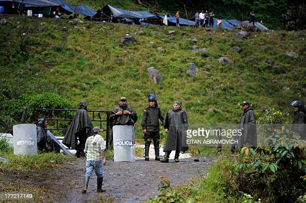 Colombian police officers stand at the entrance of an improvised camp set up by farmers in Pipiral, Meta department, during the fourth day of a...