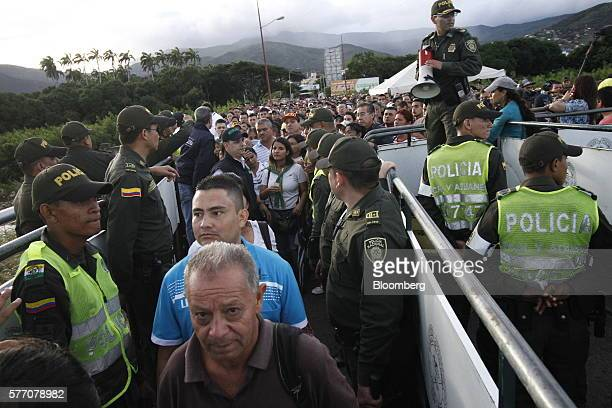 Colombian police officers stand guard as Venezuelans cross the Simon Bolivar bridge into Cucuta Colombia on Sunday July 17 2016 For only the third...