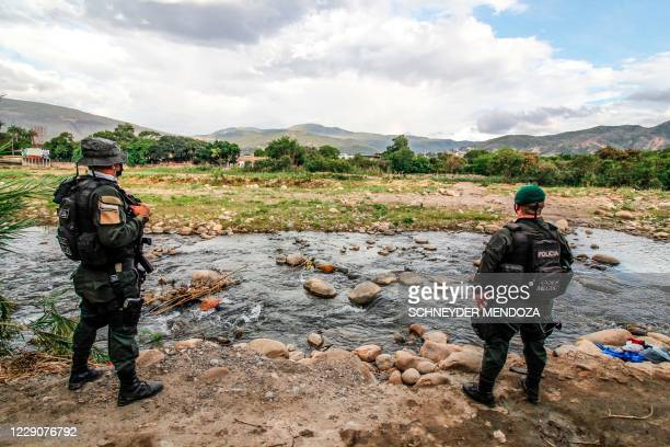 """Colombian police officers stand guard at the """"trochas"""" -illegal trails on the border between Colombia and Venezuela- near the Simon Bolivar..."""
