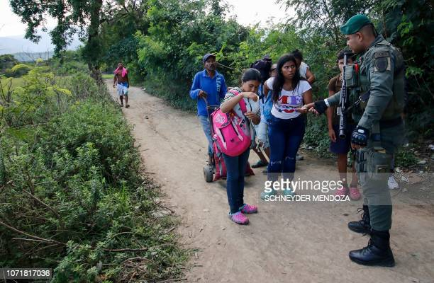 A Colombian policeman checks documents of Venezuelan migrants during a patrol along the border with Venezuela in Villa del Rosario municipality near...
