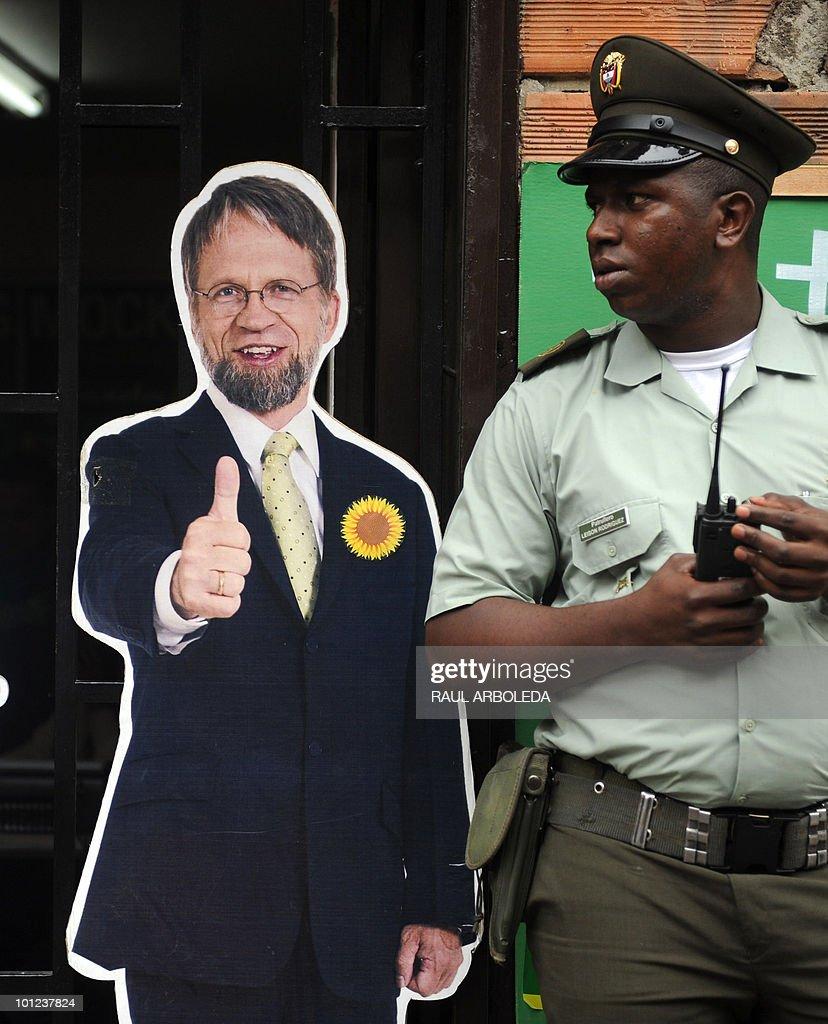 A Colombian policeman stands next to the image of Colombian presidential candidate for the Green Party Antanas Mockus (L) in Medellin, Antioquia department, Colombia on May 27, 2010. Colombia will hold presidential elections next May 30, and according to polls, a run-off election between Mockus and Juan Manuel Santos for the ruling National Unity Party, will take place on June 20. AFP PHOTO/ Raul ARBOLEDA
