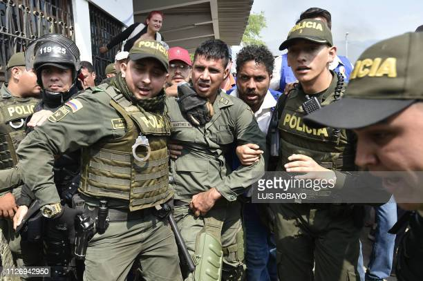 TOPSHOT Colombian policemen accompany a Venezuelan police officer who deserted from Venezuela at the Simon Bolivar international bridge in Cucuta...