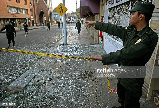 Colombian policemen cordon off an area after a blast before the house where former right wing paramilitary members lived in Bogota 15 July 2005 A...
