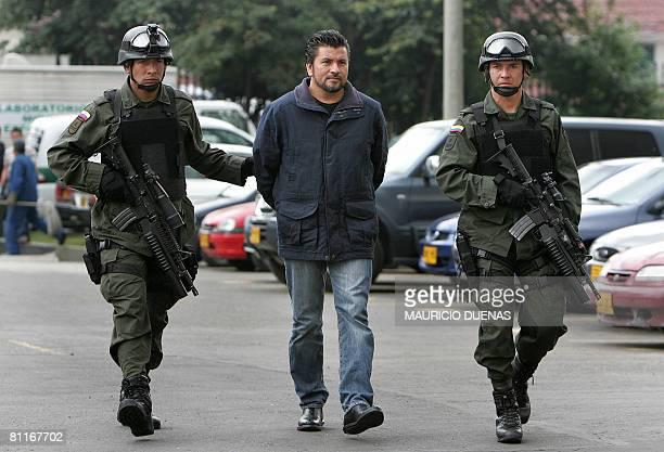 Colombian policemen escort alleged drug trafficker Gildardo Rodriguez Herrera aka The Man of the Red Shirt to a press conference in Bogota on May 20...