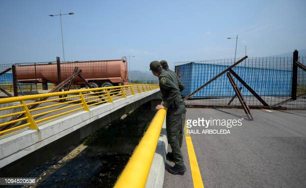 Colombian policemen look at the Tienditas Bridge which links Tachira Venezuela and Cucuta Colombia after it was blocked with containers by Velezuelan...
