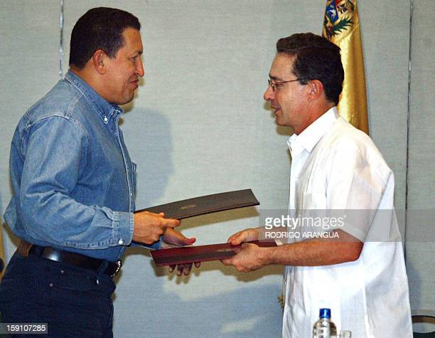 Colombian President Alavaro Uribe and Venezuela counterpart Hugo Chávez exchange documents after signing an accord 13 November 2002 in Santa Marta...