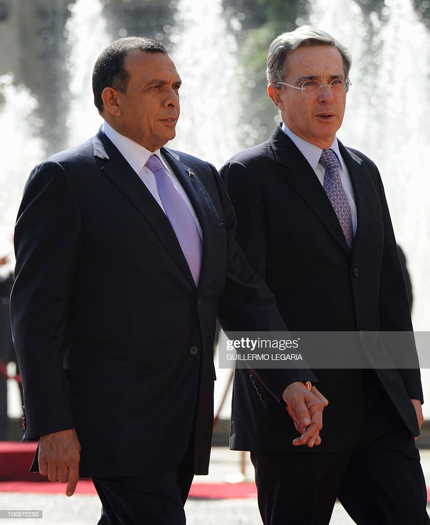 Colombian President Alvaro Uribe (R) and his Honduran counterpart Porfirio Lobo review the honor guard at Narino Palace in Bogota on May 24, 2010. Lobo is on a two-day official visit. AFP PHOTO/Guillermo Legaria