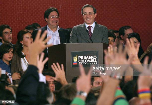 Colombian President Alvaro Uribe right and Vice President Francisco Santos smile at supporters at their campaign headquarters in Bogota Columbia...