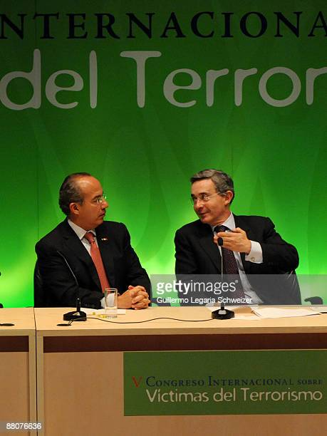 Colombian President Alvaro Uribe talks to Mexican President Felipe Calderon during the closure of the 5th Terrorism Victims International Congress on...