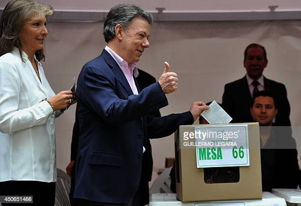 Colombian President and presidential candidate Juan Manuel Santos accompanied by his wife Maria Clemencia Rodriguez casts his vote during the runoff...