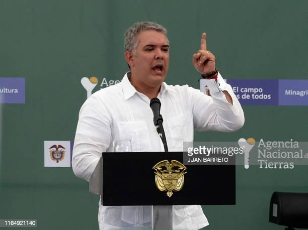 Colombian President Ivan Duque gestures as he speaks during an event to give land property deeds to conflict victims in Ovejas northern Colombia on...