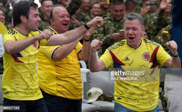 TOPSHOT Colombian President Juan Manuel Santos along with his son Esteban and members of the Colombian army celebrate as they follow on a screen the...