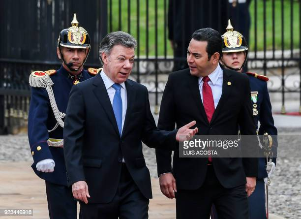 Colombian President Juan Manuel Santos and Guatemalan President Jimmy Morales talk during a welcome ceremony at Narino Palace in Bogota on February...