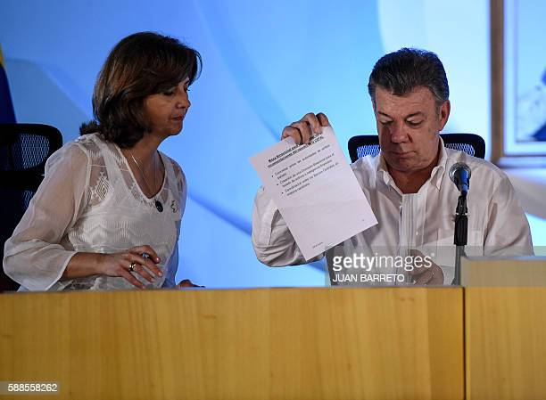 Colombian President Juan Manuel Santos and his Foreign Minister Maria Angela Holguin take part in a meeting to discuss ending a row that has kept...