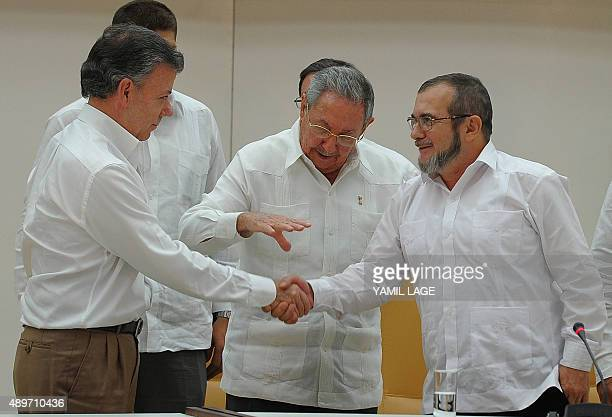 Colombian President Juan Manuel Santos and the head of the FARC guerrilla Timoleon Jimenez aka Timochenko shake hands in front of Cuban President...