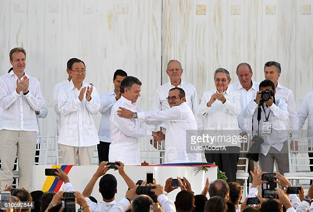 Colombian President Juan Manuel Santos and the head of the FARC guerrilla Timoleon Jimenez aka Timochenko shake hands during the signing of the...