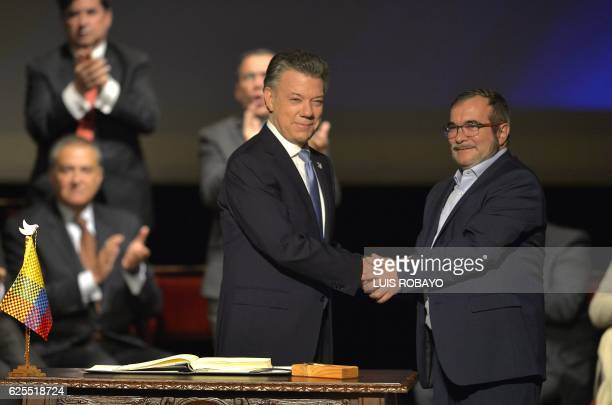 TOPSHOT Colombian President Juan Manuel Santos and the head of the FARC guerrilla Timoleon Jimenez aka Timochenko shake hands during the second...