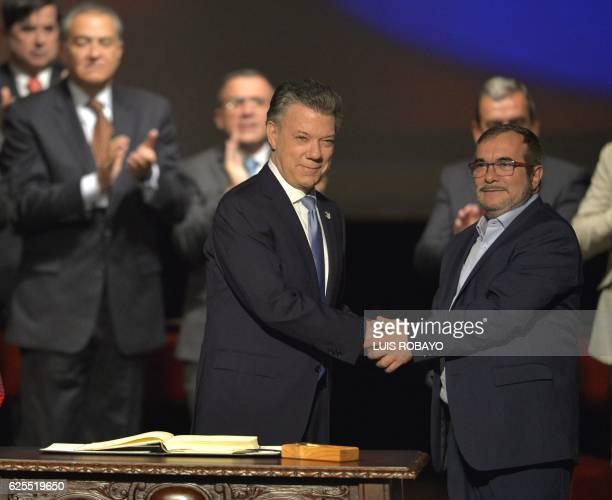 TOPSHOT Colombian President Juan Manuel Santos and the head of the FARC guerrilla Timoleon Jimenez aka Timochenko shake hands during the second...
