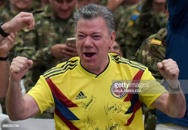 Colombian President Juan Manuel Santos celebrates as he watches the FIFA World Cup match between Colombia and Senegal at a military base in Tolemaida...