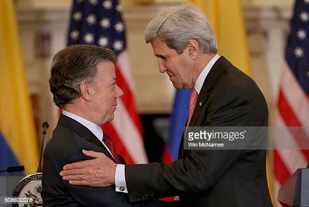 Colombian President Juan Manuel Santos is embraced by U.S. Secretary of State John Kerry following a joint press conference at the State Department...