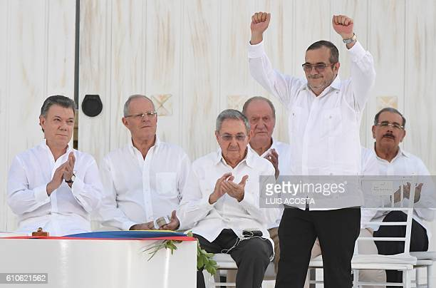 Colombian President Juan Manuel Santos looks as the leader of the FARC Rodrigo Londono better known by his nom de guerre Timoleon 'Timochenko'...