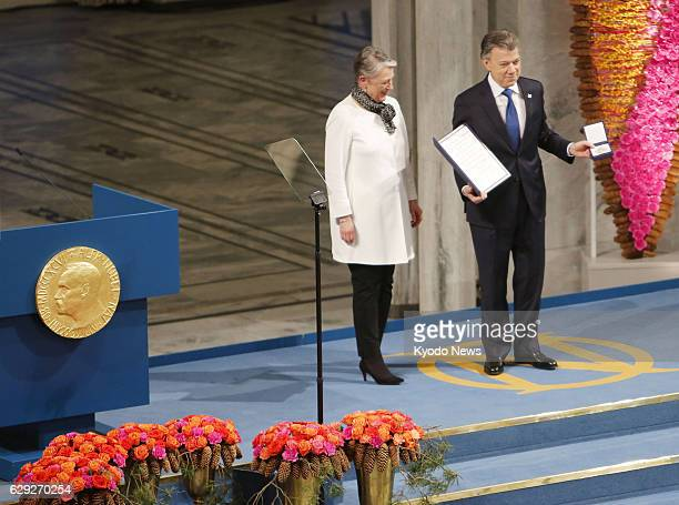 Colombian President Juan Manuel Santos poses with the Nobel Peace Prize medal and diploma at the City Hall in Oslo on Dec. 10, 2016. Santos was...