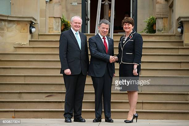 Colombian President Juan Manuel Santos shakes hands with First Minister Arlene Foster as Deputy First Minister Martin McGuinness looks on at Stormont...