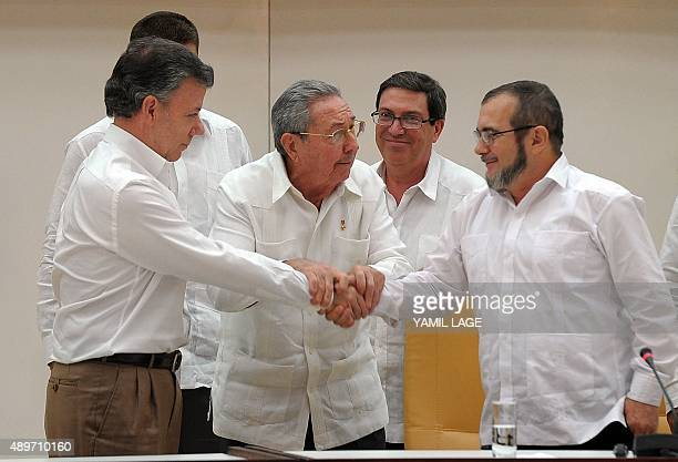 Colombian President Juan Manuel Santos shakes hands with the head of the FARC guerrilla Timoleon Jimenez aka Timochenko as Cuban President Raul...