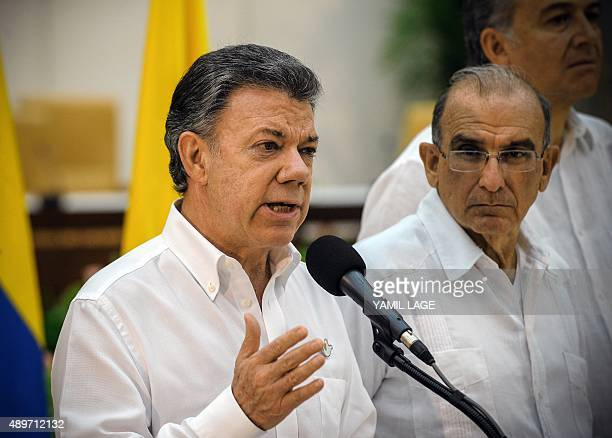 Colombian President Juan Manuel Santos speaks next to the head of the Colombian government delegation for the peace talks with the Revolutionary...