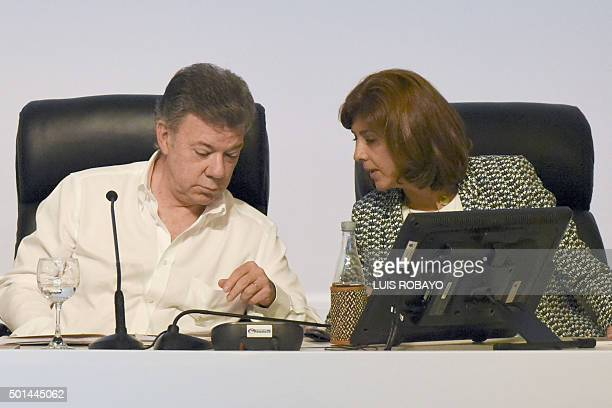 Colombian President Juan Manuel Santos speaks with his Colombian Foreign Minister Maria Angela Holguin during the Fourth ColombiaEcuador Binational...
