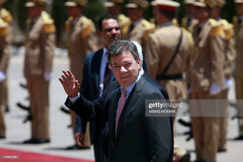 Colombian President Juan Manuel Santos waves as he reviews the honour guard during a welcome ceremony in the West Bank city of Ramallah on June 11, 2013, prior to this meeting with his Palestinian counterpart, Mahmoud Abbas. Santos is on an official visit to the region.