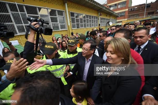 Colombian presidential candidate Gustavo Petro accompanied by his wife Veronica Alcocer greets a supporter after voting at a polling station in...