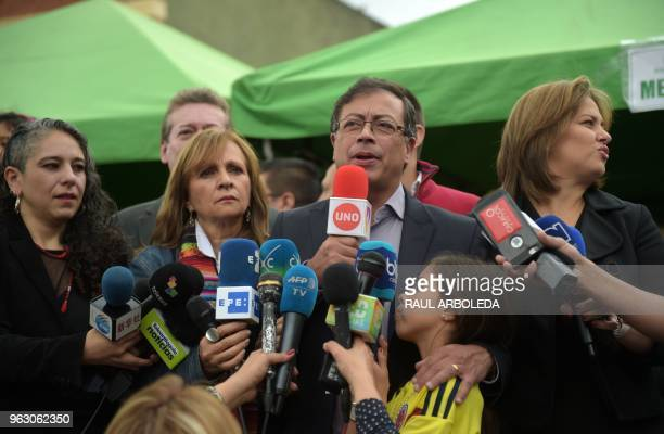 Colombian presidential candidate Gustavo Petro flanked by his running mate Angela Robledo and his wife Veronica Alcocer speaks to the press after...