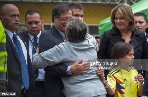 Colombian presidential candidate Gustavo Petro is greeted by a supporter as his wife Veronica Alcocer looks at a polling station in Bogota on during...