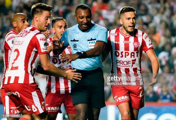 Colombian referee Gustavo Murillo argues with Argentina's Union de Santa Fe players during their Copa Sudamericana football match against Ecuador's...