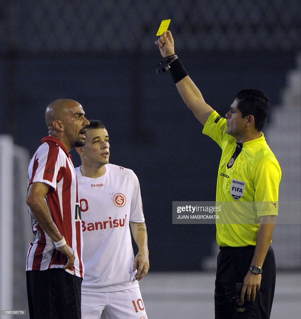 Colombian referee Oscar Ruiz (R) shows the yellow card to Estudiantes de la Plata's midfielder Juan Veron (L) and Internacional midfielder Andres D'Alessandro during their Copa Libertadores 2010 quarterfinals football match at Quilmes stadium in Buenos Aires, Argentina, on May 20, 2010. Estudiantes won 2-1 but Internacional qualied for the next round AFP PHOTO / Juan Mabromata