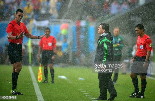 Colombian referee Wilmar Roldan gestures at Mexico's coach Miguel Herrera during the Group A football match between Mexico and Cameroon at the Dunas...