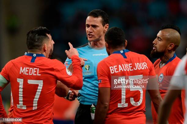 Colombian referee Wilmar Roldan listens to Chile's Gary Medel Jean Beausejour and Arturo Vidal as he conducts the Copa America football tournament...