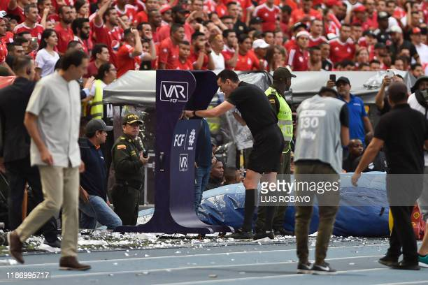 Colombian referee Wilmar Roldan looks at the VAR during the Colombian First Division Football Championship final match America de Cali and Atletico...