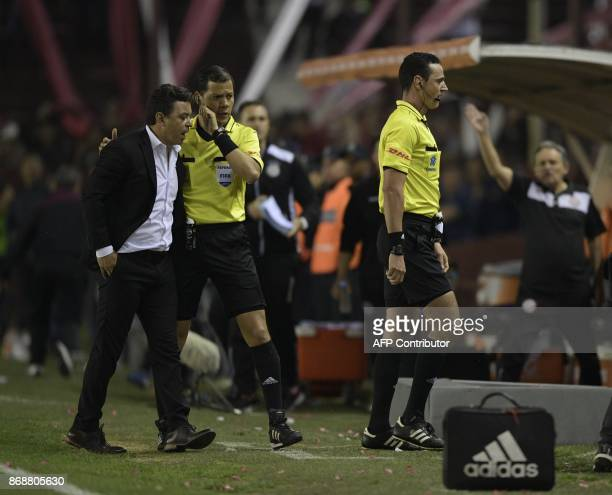 Colombian referee Wilmar Roldan steps forward to watch the screen of the VAR system before calling a penalty for Argentina's Lanus as Argentina's...