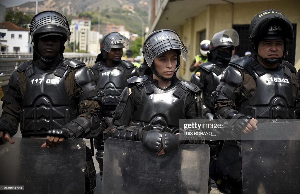 TOPSHOT - Colombian riot police guard a march in Cali, Colombia, on January 24, 2016. Thousands take to the streets to demand an increase in the minimum wage and protest the economic policies of Colombian President Juan Manuel Santos.