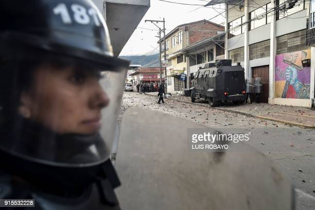 Colombian riot police officer stands guard in front of the building where Rodrigo Londono Echeverri known as 'Timochenko' the presidential candidate...