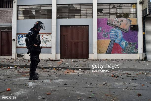 Colombian riot police officer stands in front of the building where Rodrigo Londono Echeverri known as Timochenko the presidential candidate for the...