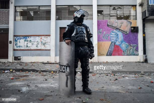 Colombian riot police officer stands in front of the building where Rodrigo Londono Echeverri known as 'Timochenko' the presidential candidate for...