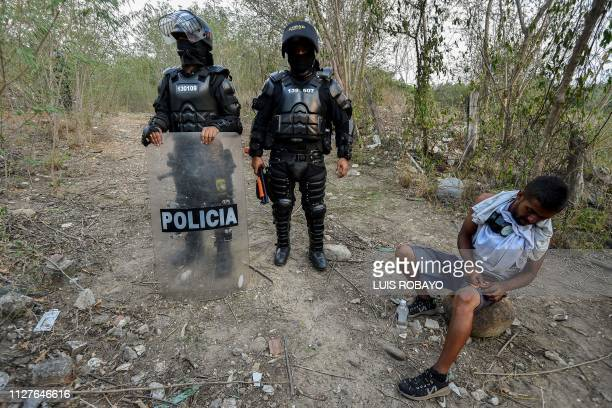 TOPSHOT Colombian riot police officers accompanied by a supporter of the Venezuelan opposition patrol the banks of the border Tachira river near the...