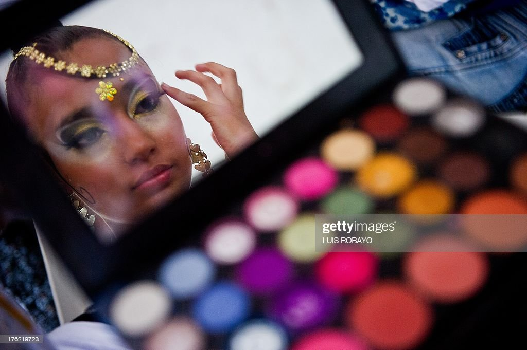 Colombian Salsa dancer Sthefania Martinez puts on make-up while backstage before her presentation during the VIII World Salsa Festival at the Cañaveralejo bullring in Cali on August 11, 2013.
