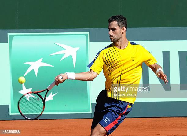 Colombian Santiago Giraldo hists the ball to Uruguayan Martin Cuevas during their Davis Cup Americas Zone Group I 2nd Round match in Montevideo on...